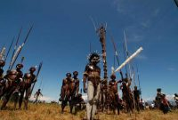 Baliem Valley Festival . Posing proudly, the tribesmen are ready to start the colossal mock war. The closer the spears hurl by the attacking tribesmen, the louder the cheers